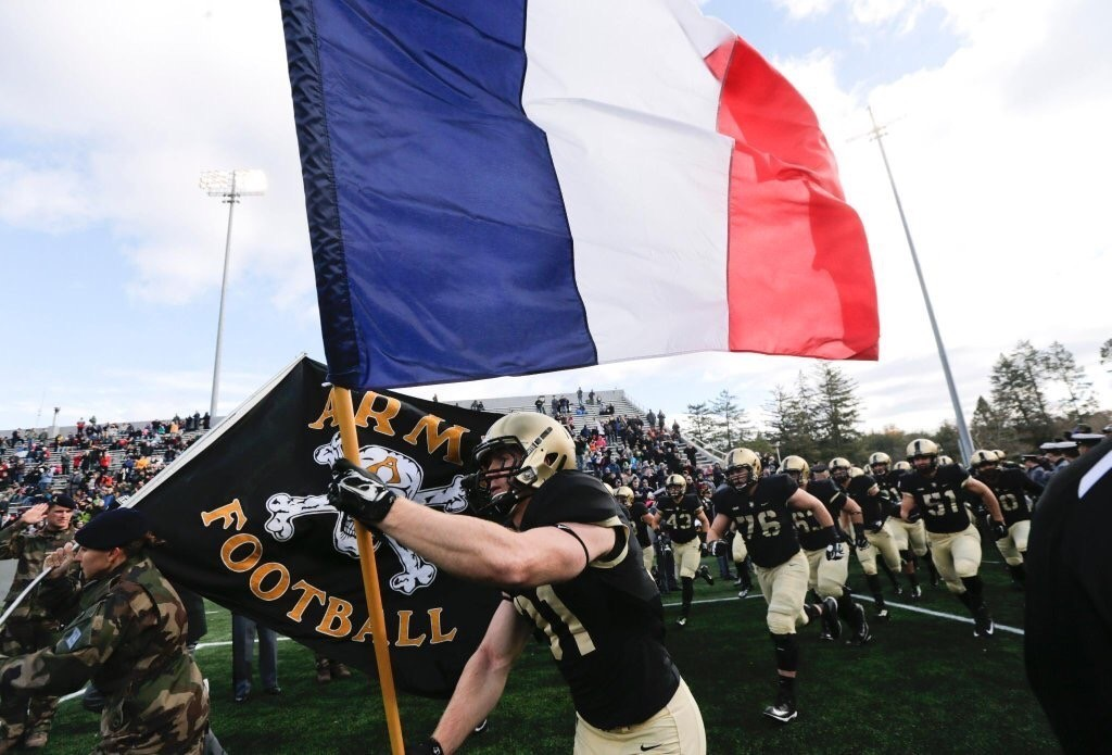 Army football players carried the France flag on the field